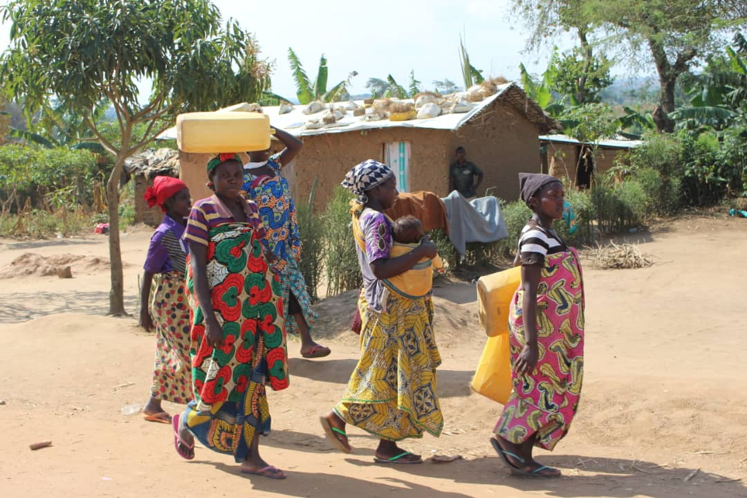 Women trek several miles to fetch water for their families in the Rwamwanja settlement (PML Daily PHOTO)
