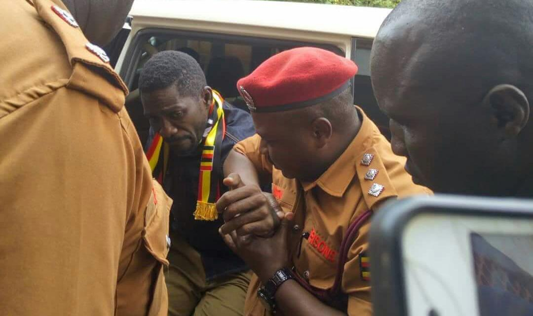 Kyaddondo East MP Robert Kyagulanyi is helped out of the van at Gulu Magistrates Court August 23 (FILE PHOTO)