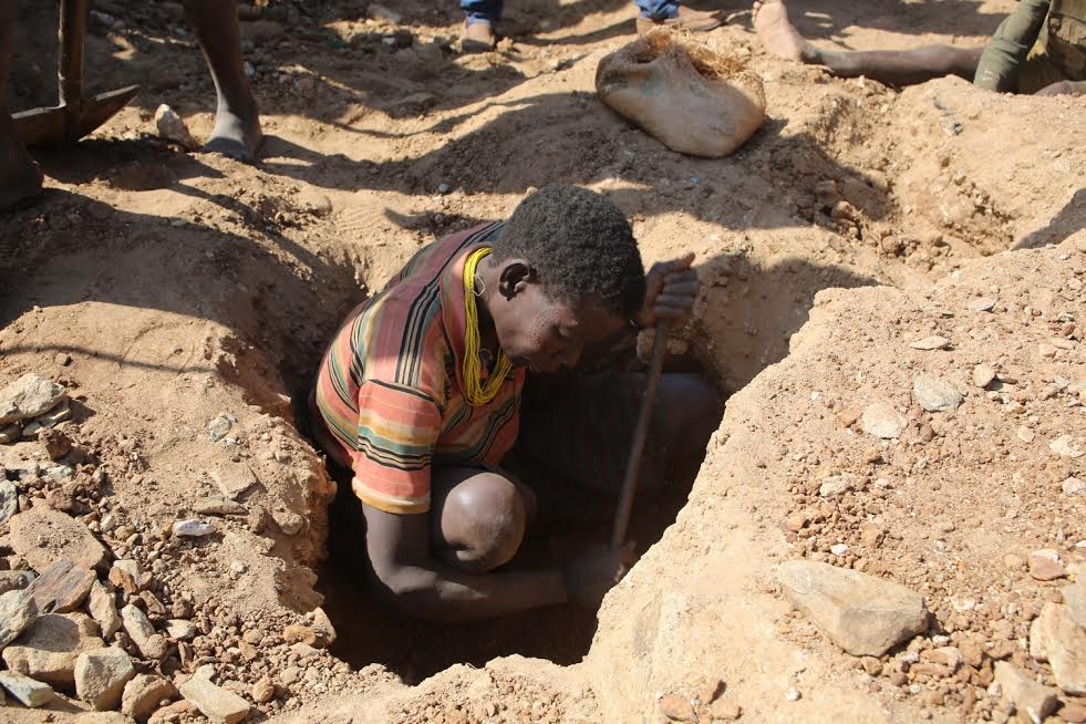 A-woman-digs-through-the-earth-to-get-Gold-for-sale-in-katikekile