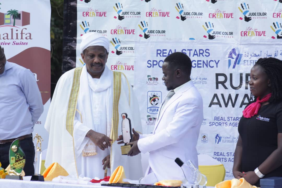 Real Stars Sports Agency president Isaac Mukasa (second right) hands over an award to Mr. Muhammed Tareq (left) of Khalif Siuts as Jude Color Soultions PR, Madrine (right) looks on (photo by Danito Nsubuga)