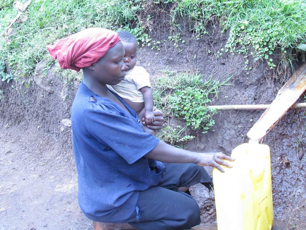 Ms Nabukwasi fetches water from the hills at a hilly spot in Soti village for drinking with her child.. David Mafabi