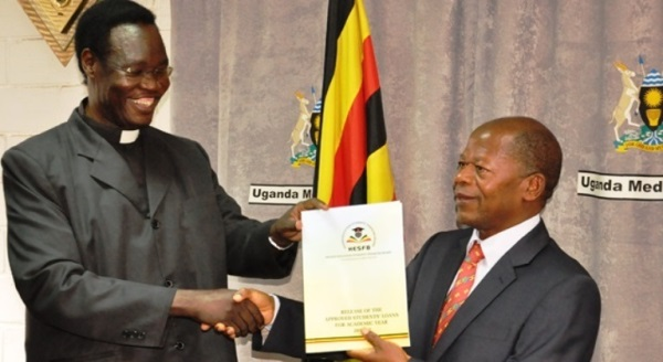Chairman of the Board handing over the List of successful Students to Hon. Minister during the release at Uganda Media Centre