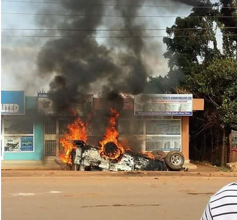 Taxi set on fire as its driver was hammered on the head by an angry solider for hitting his (solider) Toyota Land Cruiser. (Photo by Javira Ssebwami)
