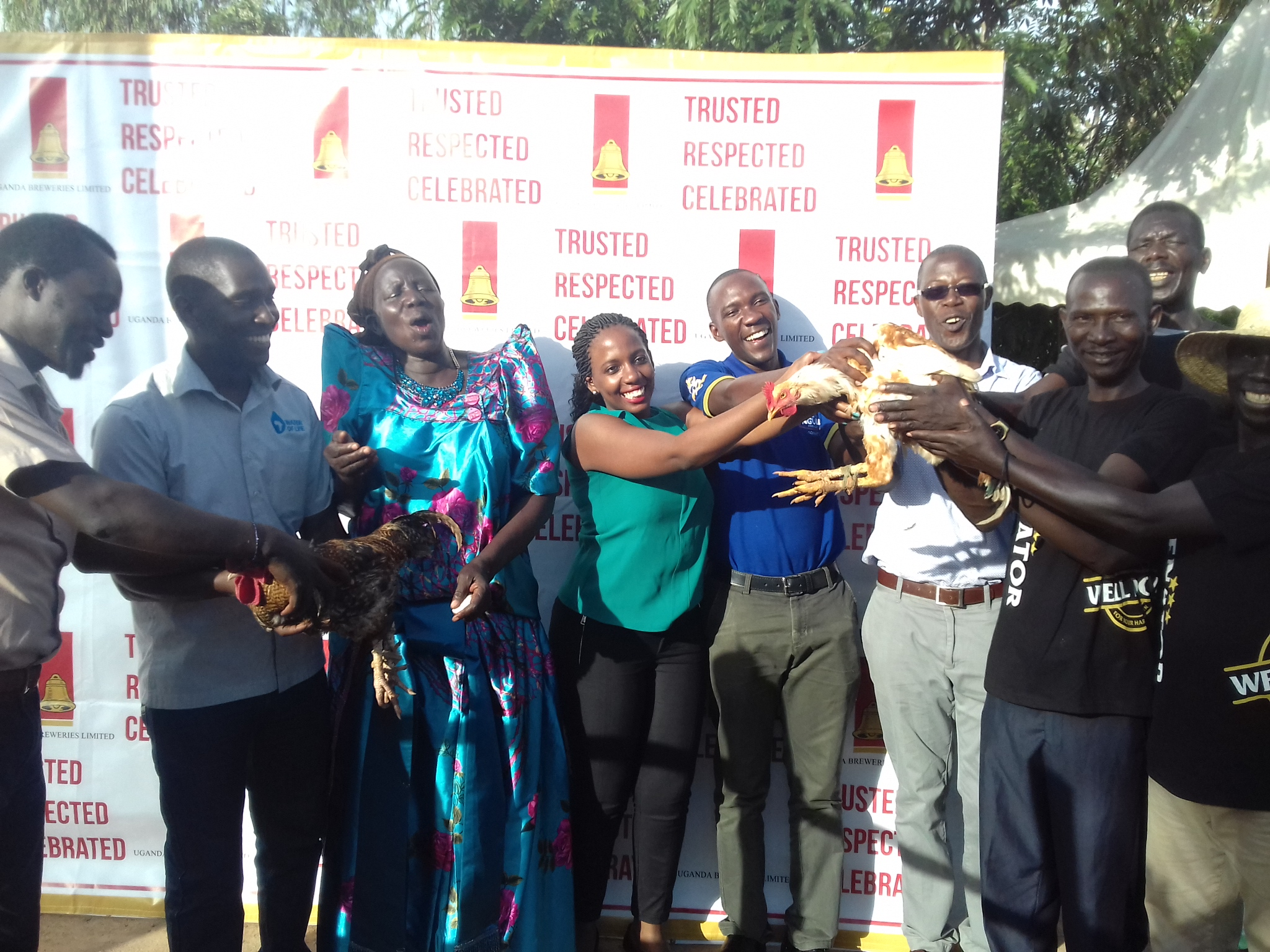 Officials of UBL receiving gifts of chicken from the community during the borehole launch in Koro Subcounty in Omoro district (PML Daily PHOTO)