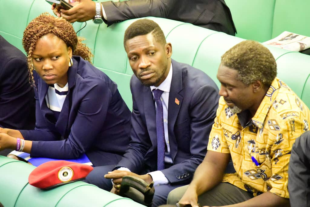 Kyadondo East MP Robert Kyagulanyi alias Bobi Wine, and Lira Municipality MP Jimmy Akena look on as legislators vote on the controversial Mobile Money tax Tuesday Oct 2(FILE PHOTO)