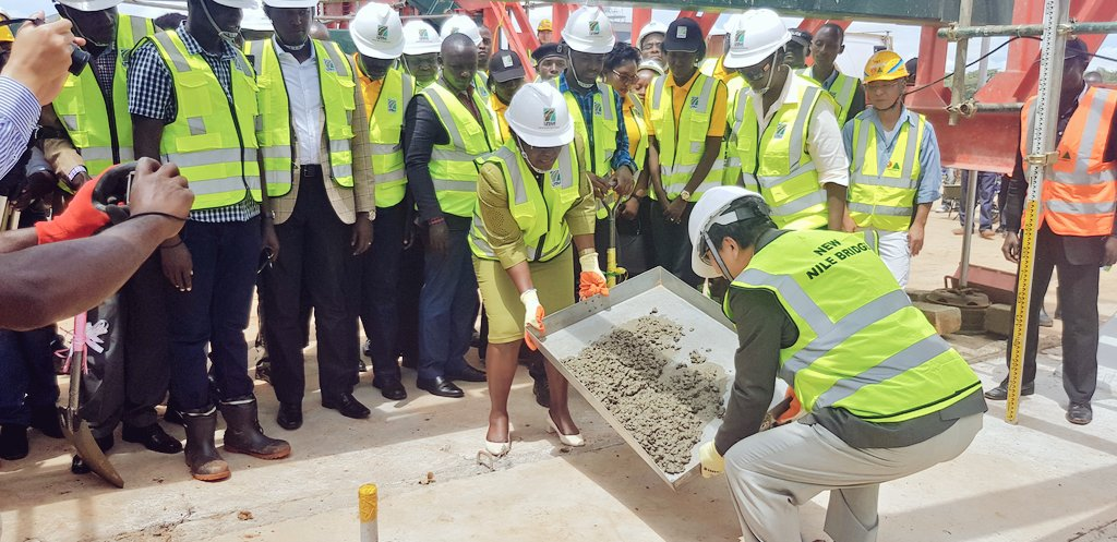 Japenese officiial look on as the Transport Minister Eng Ntege Azuba lays a milestone at the joining of the Girder at the Source of the Nile Bridge in April 2018 (FILE PHOTO)