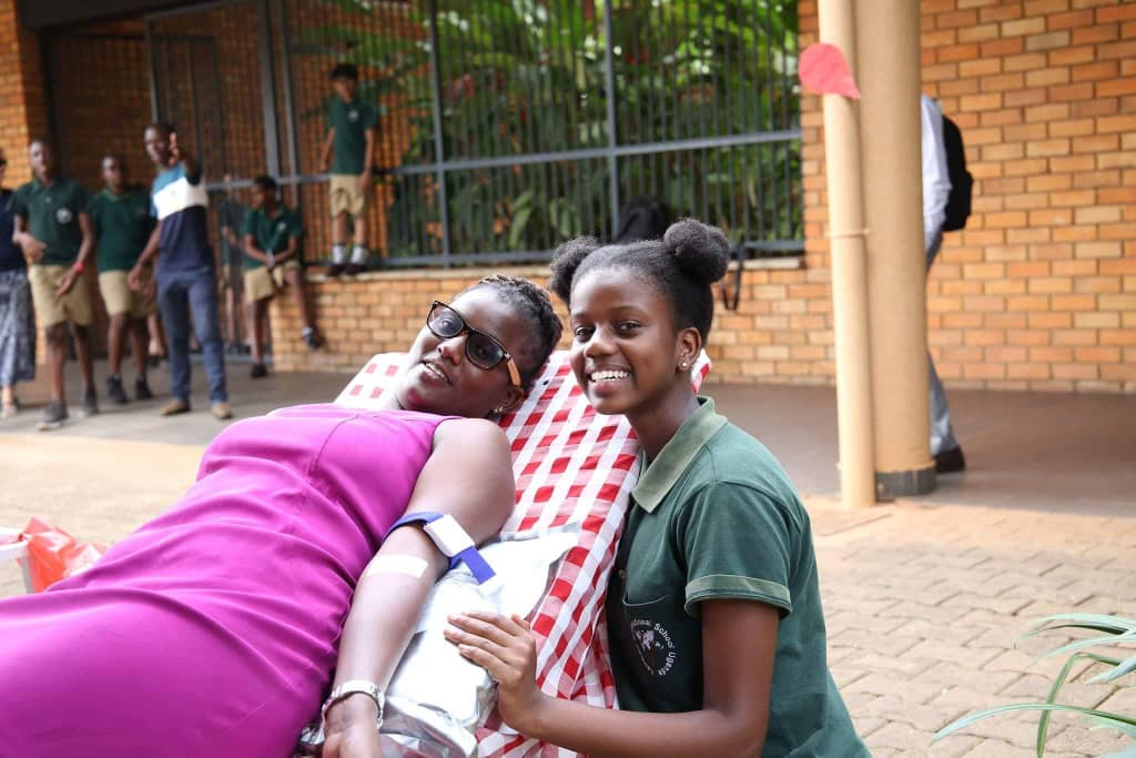 A student chats with a colleague as she takes the needle to donate blood at Kampala International School Uganda (KISU) (PML Daily PHOTO)