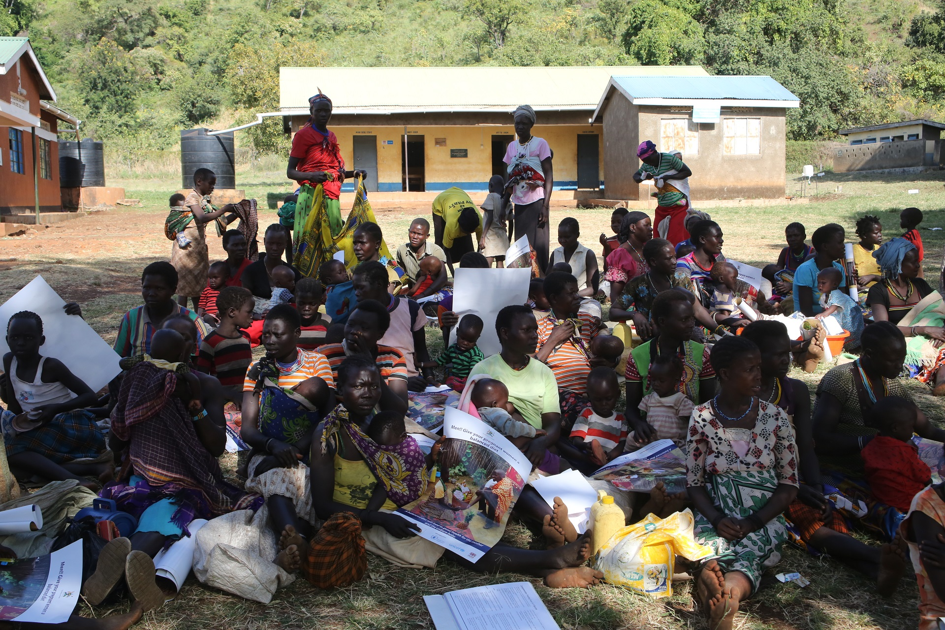 Mothers with malnurished children sit at Namalu health centre III to get food from WFP