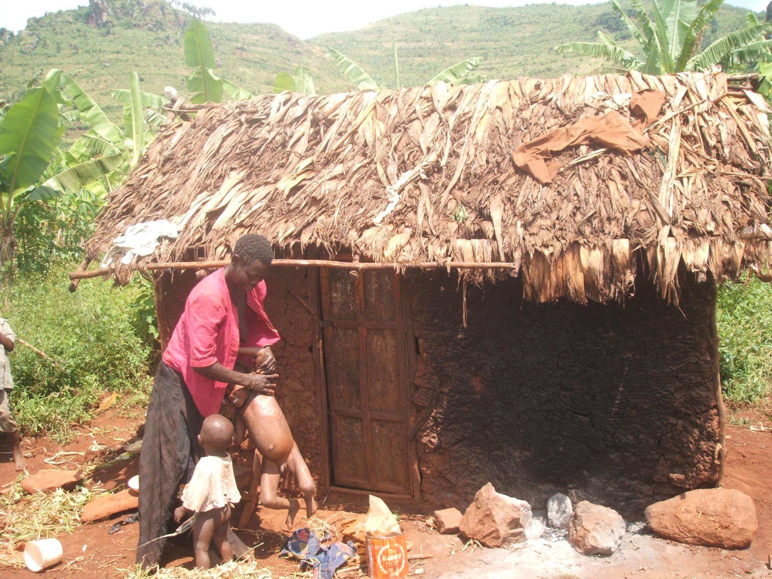 Wakooli holds off one of the children in her home. David Mafabi