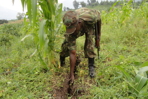 A soldier points at one of the cracks in Bumayoka Sub-county, Bududa District. PHOTO BY DAVID MAFABI