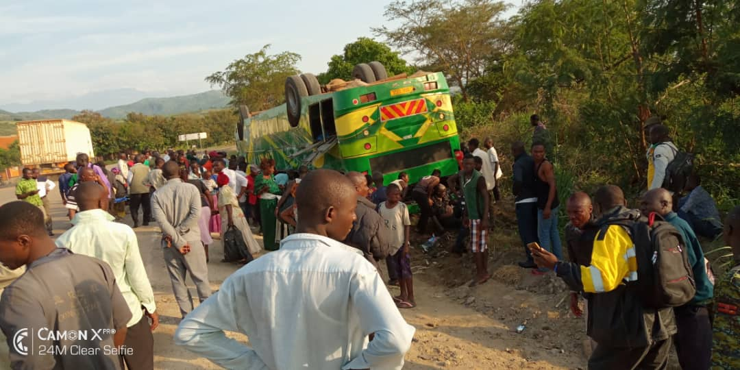 Crowd of people gathered on overturned passenger bus