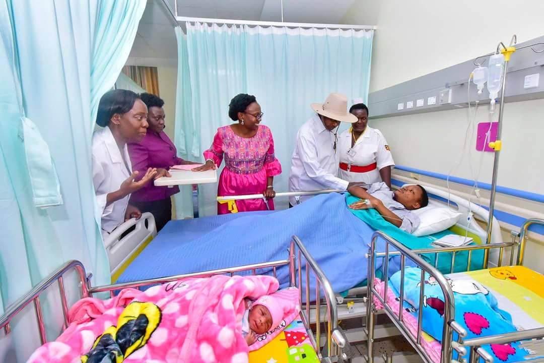 Museveni interacts with a patient at the Mulago maternal and neonatal hospital. Next to him is Health Minister, Dr Aceng