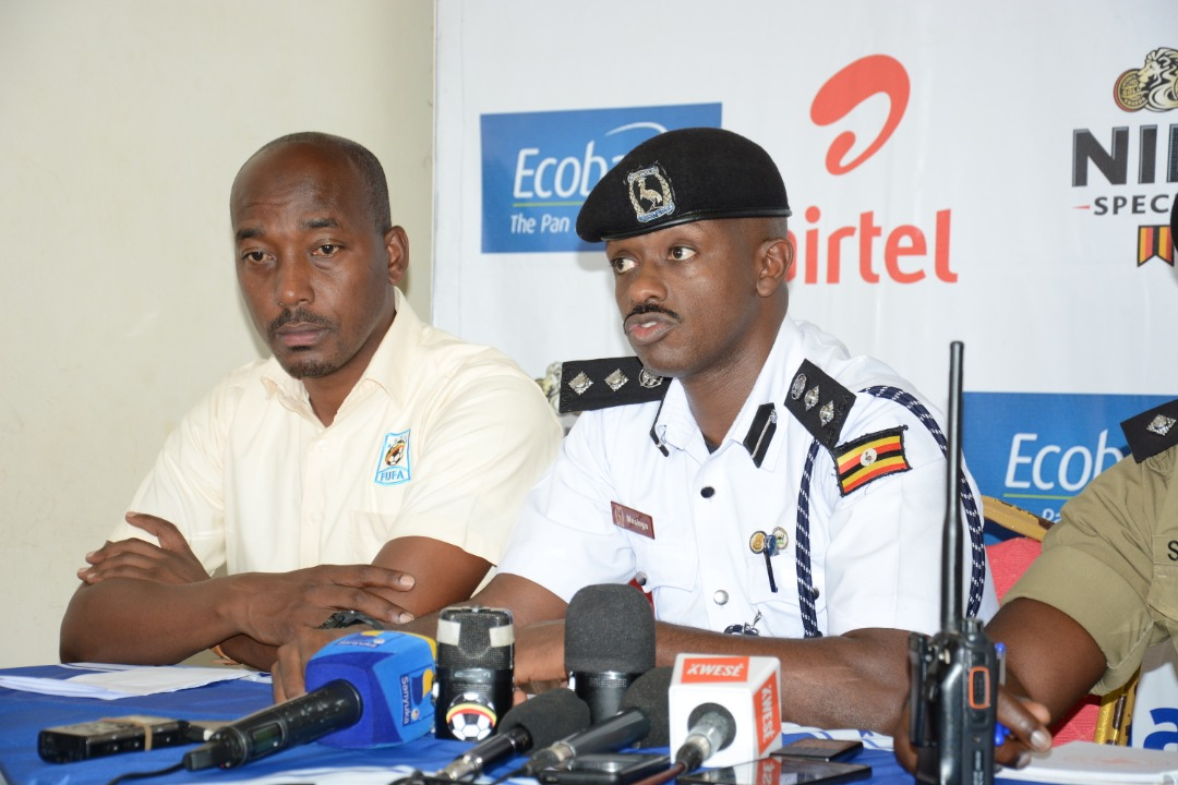 Kampala Metropolitan Traffic Police Commander, Norman Musinga address the media as the FUFA Communications manager Ahmed Hussein (left) looks on (Photo by FUFA Media)