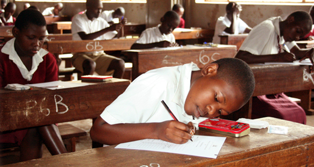 Pupils in the middle of a PLE exam. Iganga District Inspector of Schools, Mr George Tigawalana, was on Monday Nov 5 arrested for allegedly misappropriating money meant for registration of 20 pupils of Bahrain Nursery and Primary School (FILE PHOTO)