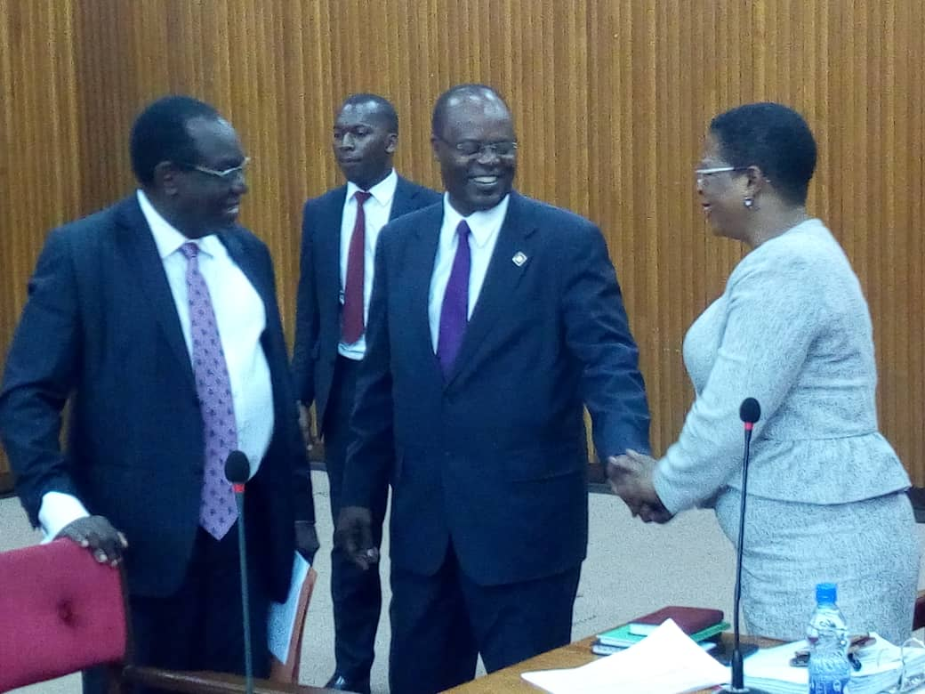 Deputy Governor Bank of Uganda,, Louis Kasekende shares a light moment with COSASE Vice Chairperson, Anita Among (Bukedea Woman MP). He affirmed that Bank of Uganda was investingating the security breach (PML Daily PHOTO)