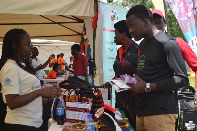 An exhibitor from Mama Club Uganda attending to some of the visitors during the exhibition on  November 29 in the Makerere University Freedom Square (PHOTO By NINSIIMA JULIAN)