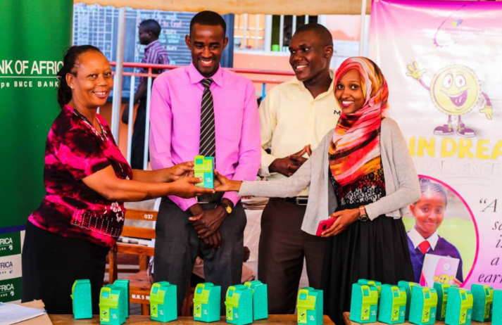 (L). Headmistress of Mirembe Junior receives a Coin piggy Bank from Aisha Ali CEO l-Foundation while teachers look on. (PHOTO BYABRAHAM MUTALYEBYA)