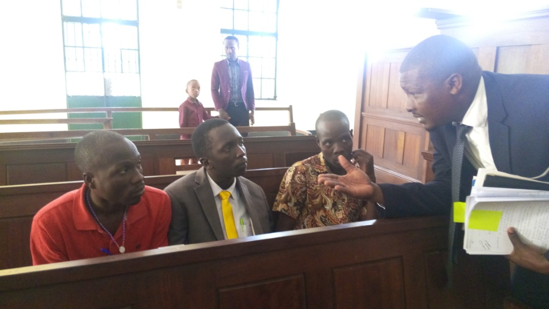 Bagyenda (middle) listens to his c0-accused's lawyer after court.