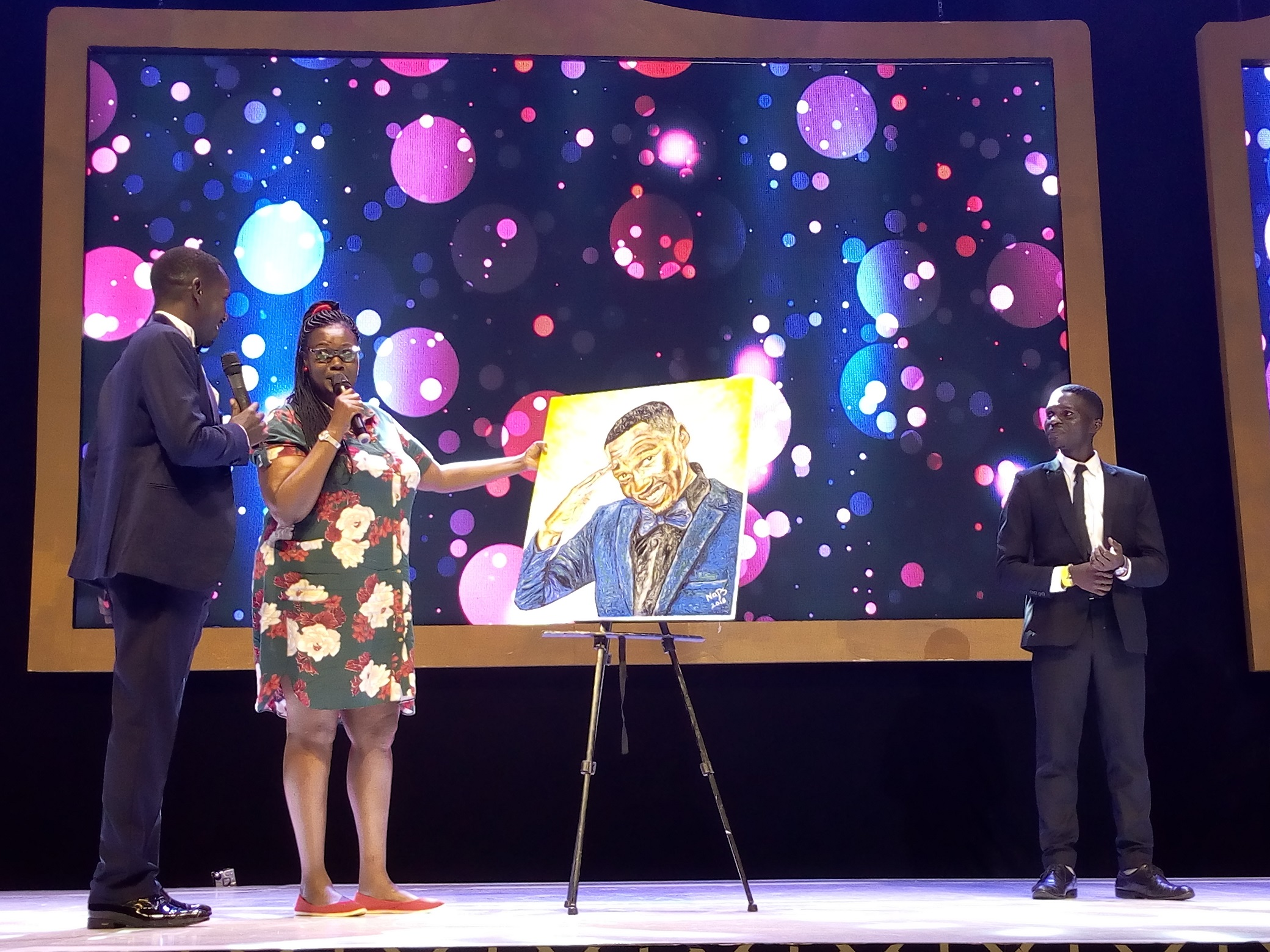 Pablo  and Hon Muhanga Margaret doing of the Souvenior Artpiece as Nasuru the artist looks  on last Evening at Kampala Serena Hotel.