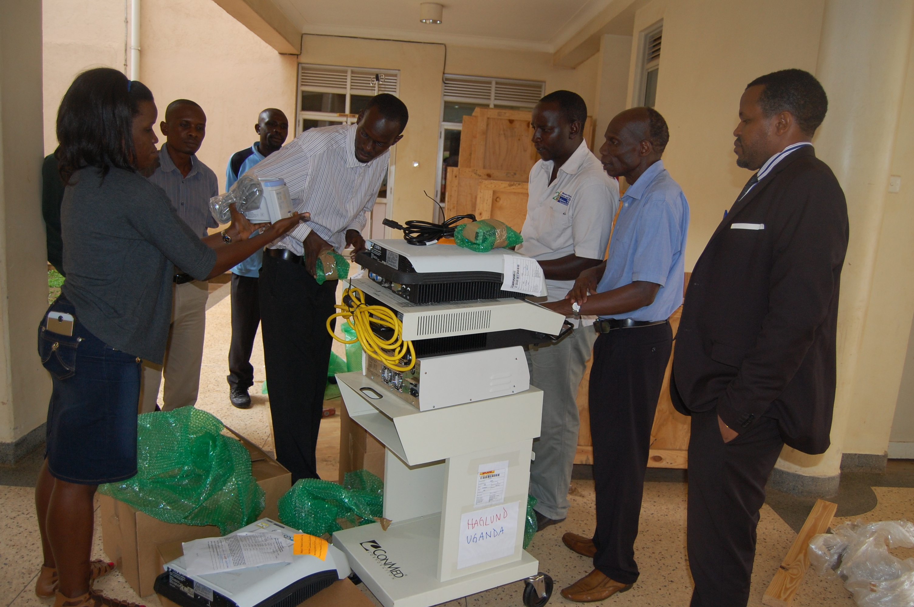 L-R. Dr. Barigye, Prof. Kitya openning the consignment of asorted medical equipments on friday