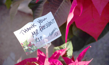 A note at a makeshift memorial in tribute to former US President George H. W. Bush is pictured outside a gated community where Bush lived in Houston, Texas, on December 2, 2018.