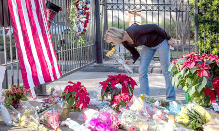 A mourner leaves flowers at a makeshift memorial in tribute to former US President George H. W. Bush outside a gated community where Bush lived in Houston, Texas, on December 2, 2018.