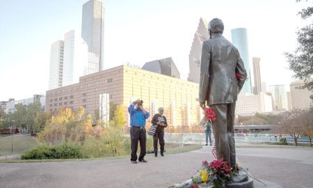 A man photographs a makeshift memorial in tribute to former US President George H. W. Bush at a monument in his honor in Houston, Texas, on December 2, 2018.