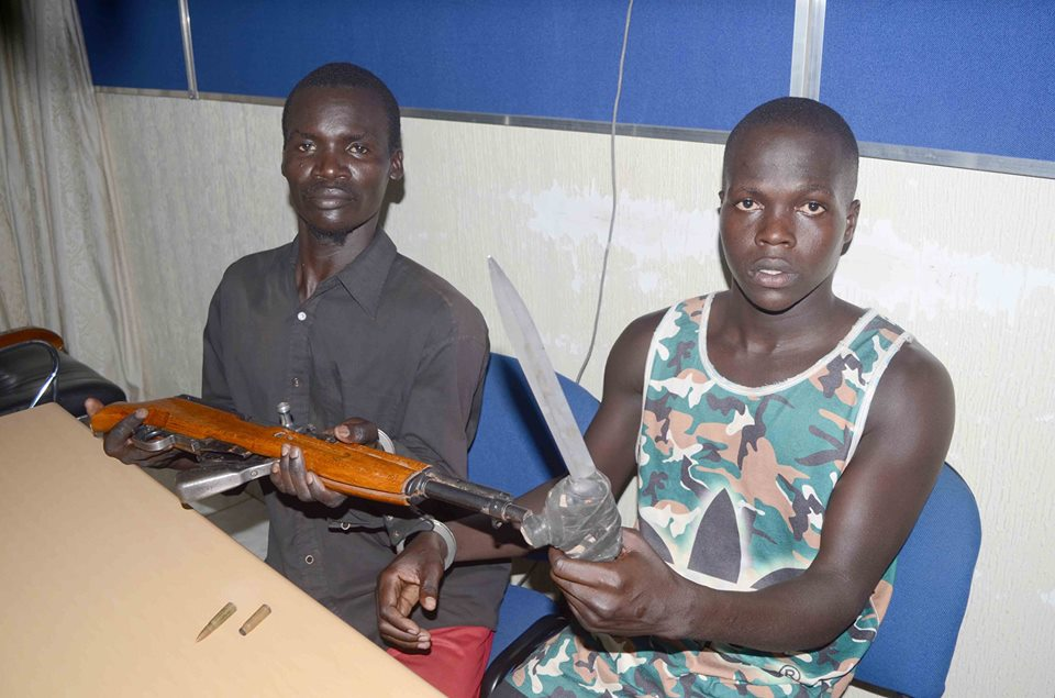 Lawrence Okello and Anthony Ouma holding a gun and machete they use while robbing. (POLICE PHOTO)