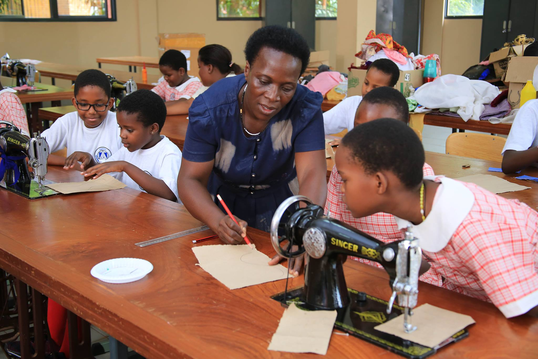 Kampala Parents' pupils attend a home economics lesson in the stitching room. The school believes in balanced education. The school's founders also believe that strengthening Uganda's sustainable wealth creation, employment and inclusive growth, requires equipping children with globally competitive skills, relevant knowledge and positive attitudes