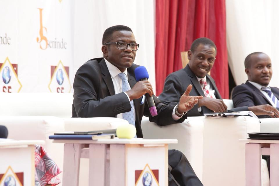 Kattikiro Mayiga (left) speaking at the Workshop as fellow panelists Kiryowa Kiwanuka (center) and Patrick Kanyomozi (right) look on.