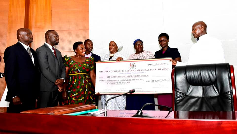 President Museveni hands over a cheque to the YLF youths beneficiaries in Hoima District as he tipped youth and women on Poverty (PPU PHOTO)