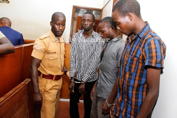 A prison warder holds the hand of Brian Bagyenda with Innocent Bainomugisha and Vincent Rwahwire (FILE PHOTO)