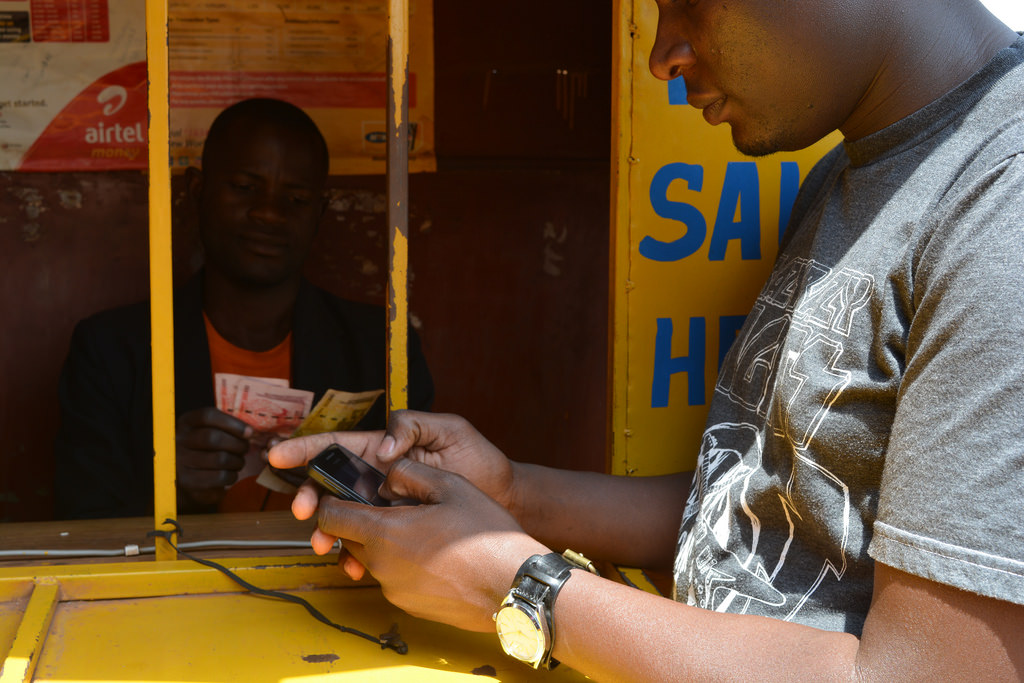 A client transacts with mobile money at an agent kiosk. Police in Tororo have mounted a search for mobile money fraudsters in a renewewd fight against fraud. (FILE PHOTO