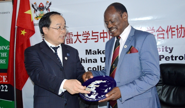 UPC Vice President-Prof. Jun Yao (L) explains the inscriptions on a souvenir shortly after handing it over to Prof. Barnabas Nawangwe (R) after the Agreement signing ceremony, 7th January 2019, Makerere University, Kampala Uganda. (PML PHOTO)