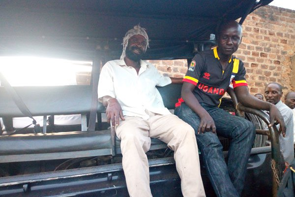 Paul Kiveyiganga (left) who operates the scrap shop on a police patrol truck after his arrest.