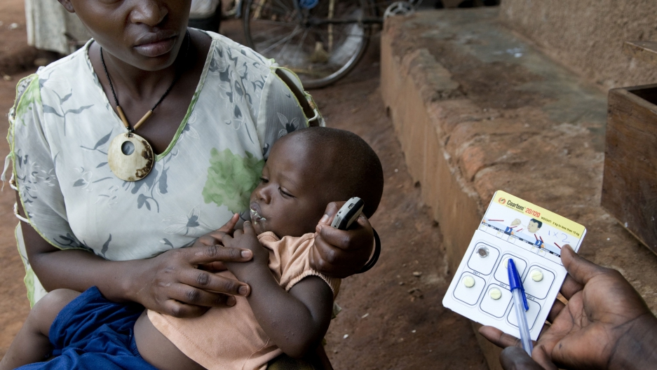 A health worker prescribes medicine for a child with Malaria.