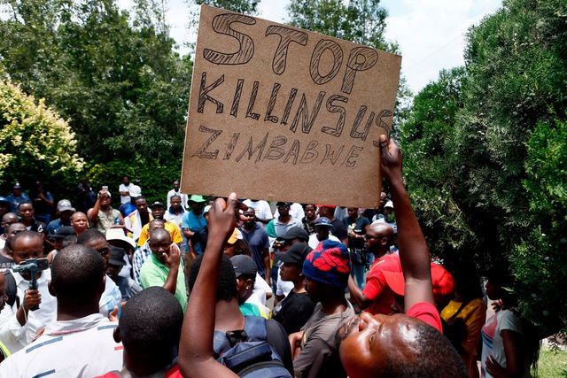 A protester holds a placard during a demonstration of Zimbabwean citizens outside the Zimbabwean Embassy in Pretoria on January 16, 2019, following the announcement of a petrol price hike in Zimbabwe and the recent shut down of mobile phone networks and internet services. - Three people were shot dead on January 15 and many were injured when Zimbabwean security forces cracked down on protests triggered by the president's announcement on January 13 that fuel would more than double in price as the country's economic crisis deepens. Zimbabwe's mobile phone networks and internet were shut down for the second day on January 16. (Photo by Phill Magakoe / AFP)        (Photo credit should read PHILL MAGAKOE/AFP/Getty Images)