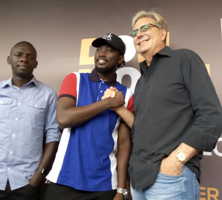 Levixone shakes  hands with Don Moen as Pastor Bugembe looks on.