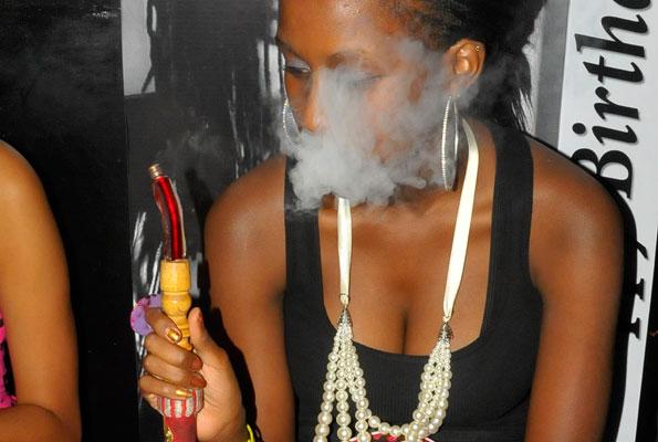 A young woman enjoys smoking pot 'Shisha'. Police swang in action arresting 18 (FILE PHOTO)