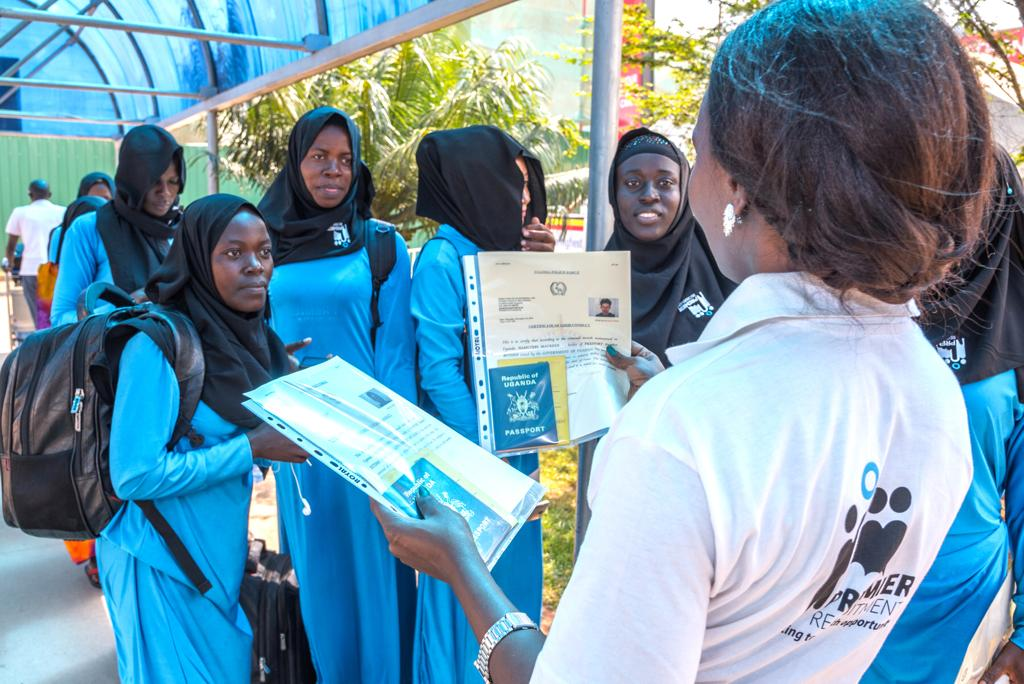The girls get last minute advice and their documentation from Ms. Marley Ritah(left), the Premier Recruitment Ltd External Recruitment Operations Manager at Entebbe Airport.