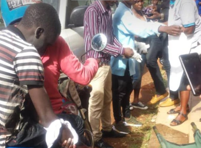 A Kyambogo University student identified as Abraham being rushed for medication after losing a hand in school fees protest on Thursday. (COURTESY PHOTO)