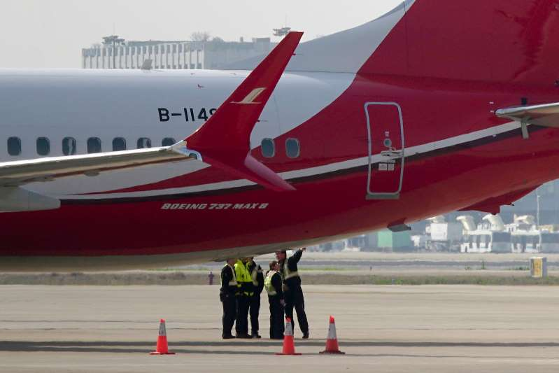 Ground crew chat near a Boeing 737 MAX 8 plane operated by Shanghai Airlines parked on tarmac at Hongqiao airport in Shanghai, China, Tuesday, March 12, 2019 (ASSOCIATED PRESS PHOTO)
