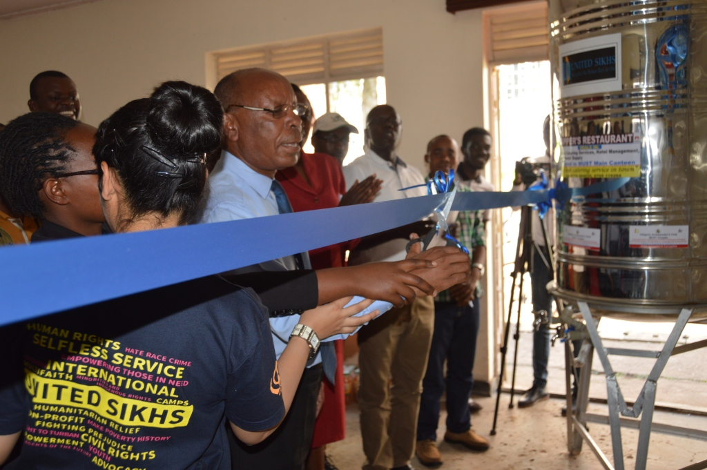 Emmanuel Kyagaba Dean of students MUST cutting the ribbon as he commissioned the water filter