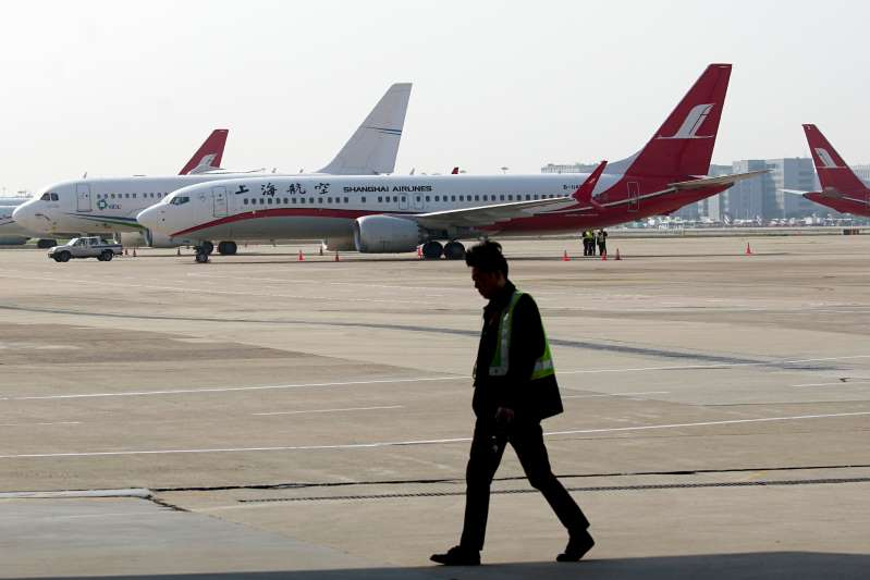 A ground crew walks near a Boeing 737 Max 8 plane operated by Shanghai Airlines parked on the tarmac at Hongqiao airport in Shanghai, China, Tuesday, March 12, 2019 (ASSOCIATED PRESS PHOTO)