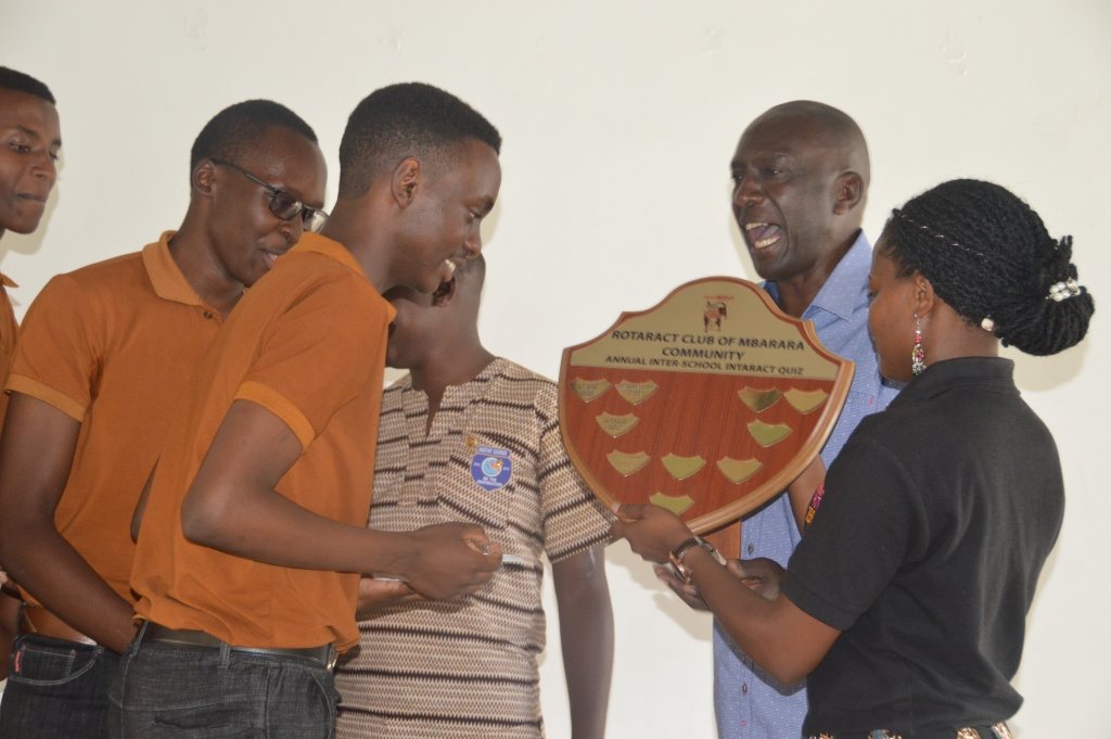 Mbarara High school interact club president recieving the shield from Balam Kasisi as Assistant Governor Apollo Ampumwize look on (1)