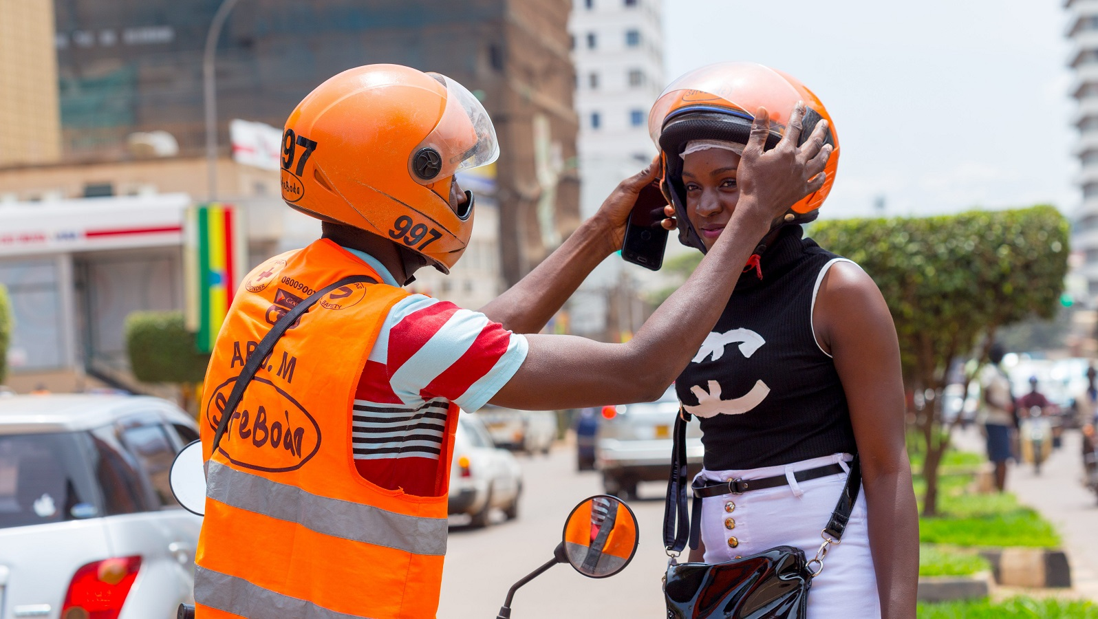 A safe boda rider helps a womn wear her helmet(FILE PHOTO)