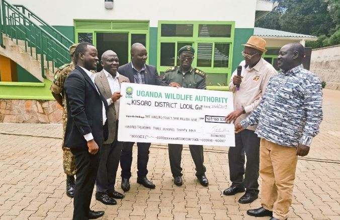 Minister of Tourism, Ephraim Kamuntu (2nd R) and UWA's Sam Mwandha (C) handing a dummy cheque to district officials. (PHOTO/PML Daily)