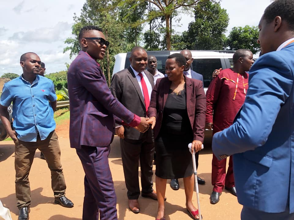 Singer Chameleon shakes hand with Hon. Betty Nambooze after they have been denied access to their colleague in prison.