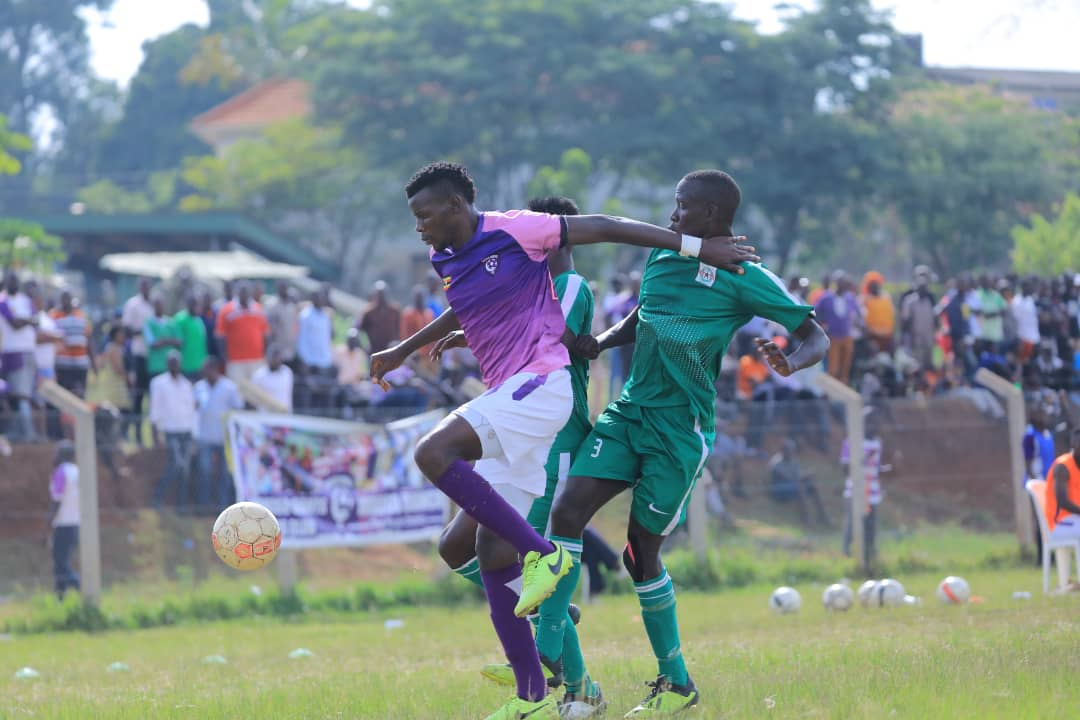 Karim Ndugwa tries to hold off two UPDF players at Bombo on Thursday. (WAKISO PHOTOS)