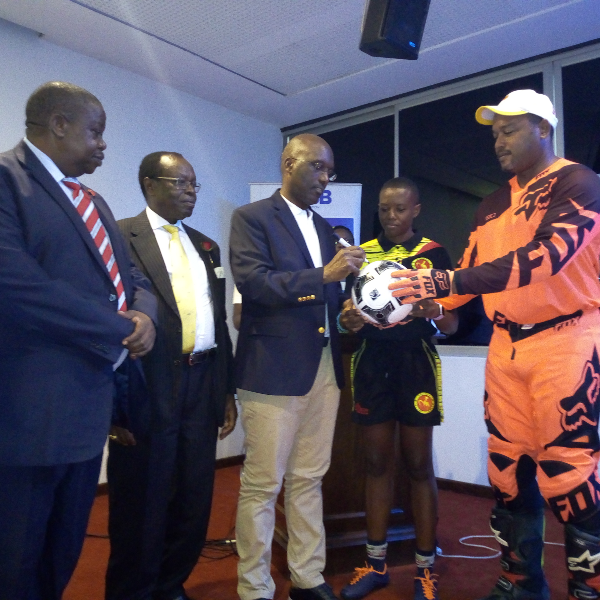 .L - R  Hon Kahinda Otafiire, Minister of Justice & Constituitional Affairs, Ambassador Francis Butagira , Chaiperson URSB , Mr.Bemanya Twebaze, Registrar General,URSB signing on the ball in presence of the Sports Ambassadors of URSB, Charlotte Mudola and Arthur Blick Jnr( Photo/ Abraham MUTALYEBWA)